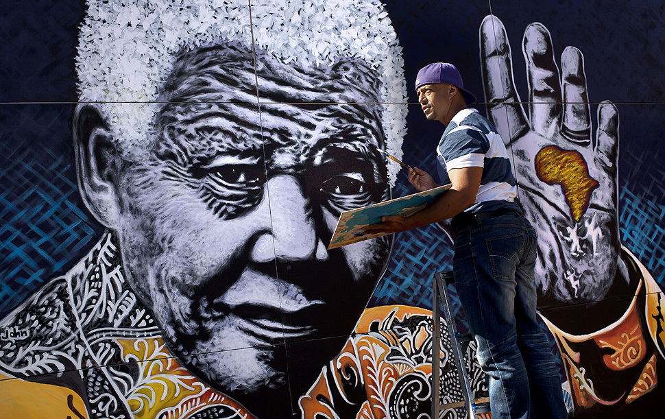 South African artist John Adams works on a giant acrylic-on-canvas painting of Nelson Mandela