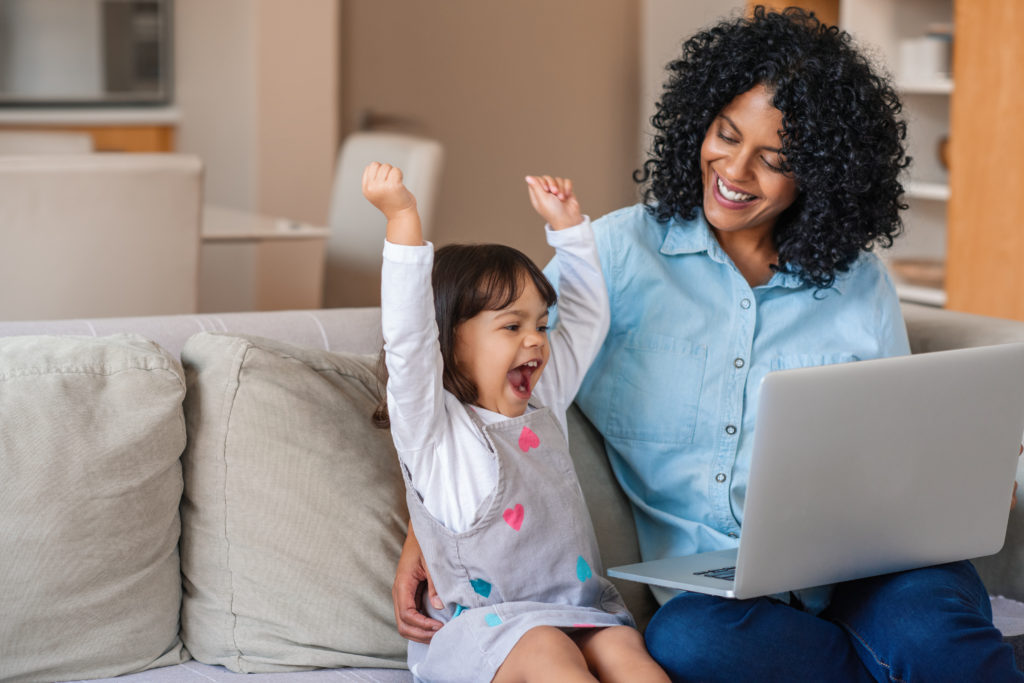 Excited little girl and mother watching something on a laptop